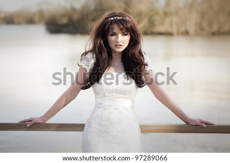 Beautiful bride on a bridge in front of lake. - stock photo