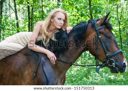 Beautiful bride on horseback in the forest - stock photo