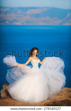 Beautiful Bride outdoor Portrait, wedding at sea, newlywed woman happy smiling, marriage day girl in white dress on rocks, soft light, series - stock photo
