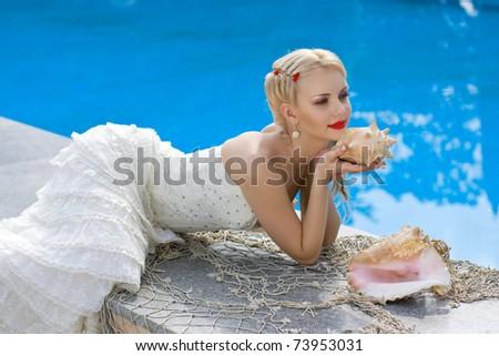 beautiful bride posing near pool with sea shells - stock photo