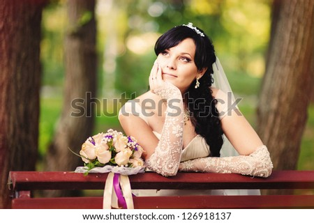 Beautiful bride posing with a flowers in her wedding day  in a park. wedding dress. Bridal wedding bouquet of flowers - stock photo