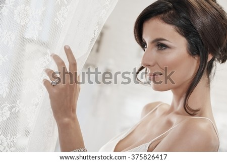 Beautiful bride preparing for wedding-day. Side view. - stock photo