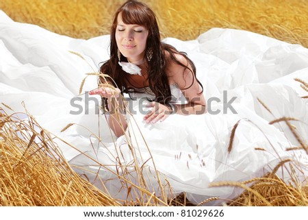 Beautiful bride relaxing in a field of rye - stock photo