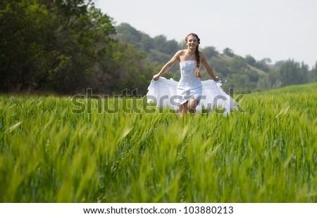Beautiful bride running on the grass field - stock photo