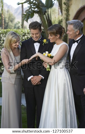 Beautiful bride showing his wedding ring to mother in law with family standing together - stock photo