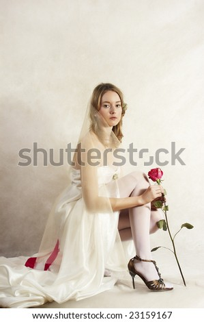 beautiful bride sits with a red rose - stock photo