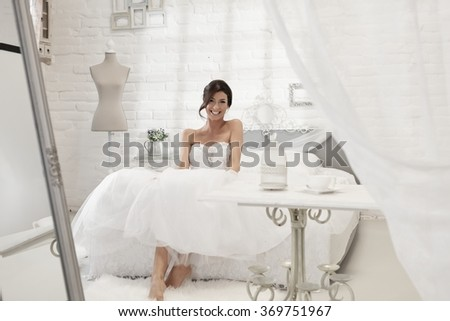 Beautiful bride sitting on bed in white bedroom, smiling happy. - stock photo