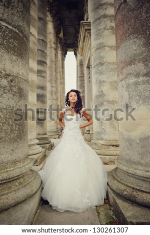 beautiful bride stands between the  columns of the an old church in west Ukraine - stock photo