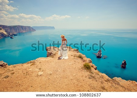 beautiful bride stands on the precipice of a blue sea - stock photo