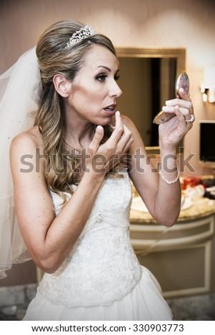 Beautiful bride touches up makeup - stock photo