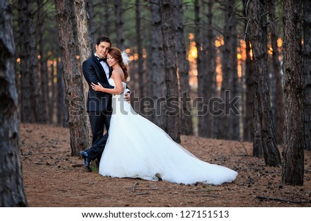 beautiful bride with a handsome groom at the forest - stock photo