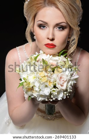 Beautiful bride with bouquet of flowers - stock photo