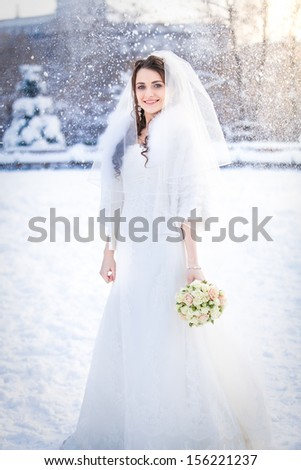 Beautiful bride with bouquet posing outdoor in snow - stock photo
