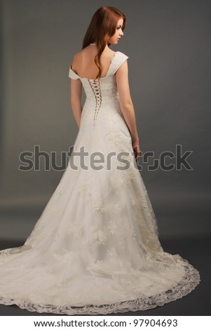 beautiful bride with curly red hair in luxury wedding dress with tail - stock photo