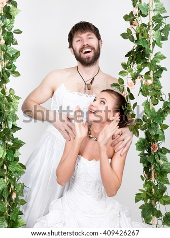 Beautiful bride with fashion wedding hairstyle. bearded bridesmaid, the bride on a swing. Bride in horror - stock photo