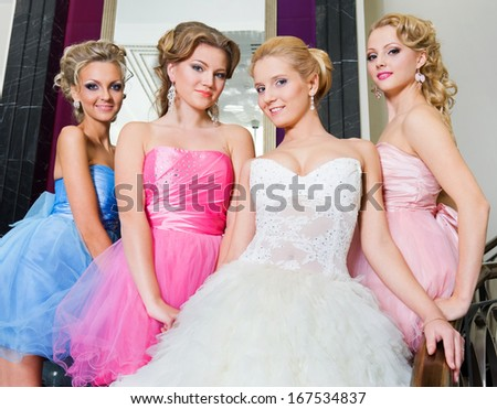 Beautiful bride with her  bridesmaids in the beautiful interior - stock photo