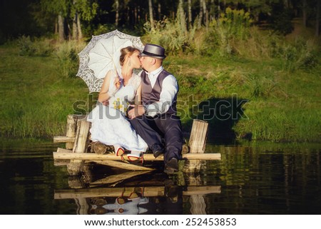 Beautiful bride with umbrella and groom kiss on the bridge - stock photo