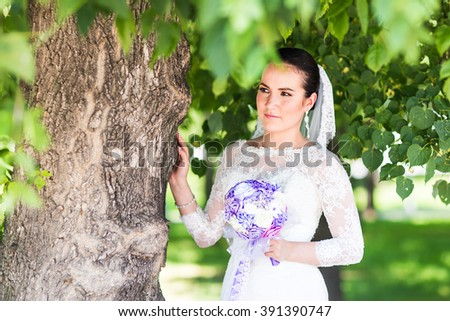 Beautiful bride with wedding bouquet of flowers outdoors in green park - stock photo