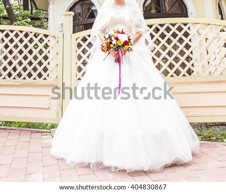 Beautiful bride with wedding bouquet of flowers outdoors in  park. - stock photo