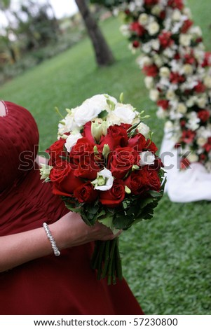 Beautiful bridesmaid holding a wedding bouquet of roses. - stock photo