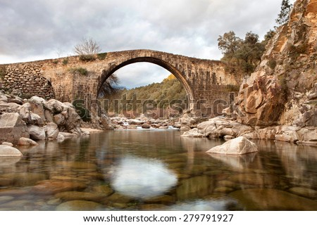 Beautiful bridge with a clear river in mountain of Spain - stock photo