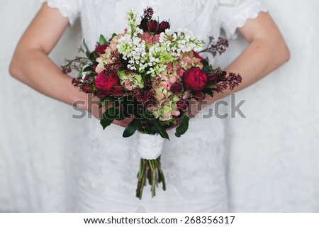 Beautiful bright bridal bouquet in bride hands  - stock photo