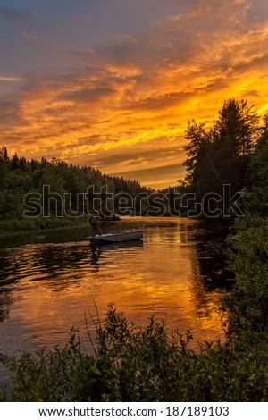 Beautiful bright dramatic sunset over river with man standing on his feet in boat and forest along riverside. Arkhangelsky region, Russia.  - stock photo