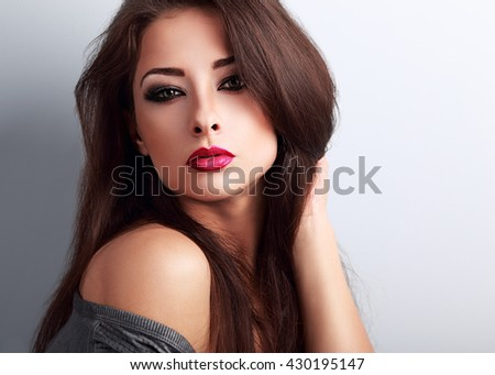 Beautiful bright makeup woman with red lipstick looking hot on blue background. Closeup portrait - stock photo