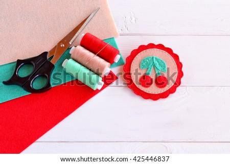 Beautiful bright summer felt brooch, felted brooch handmade. Hand embroidery. Textile art, felt jewelry. Scissors, colored thread, a needle, a set of multicolored felt  - stock photo
