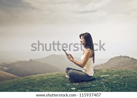 Beautiful brown girl, in a wasteland, using a tablet pc - stock photo
