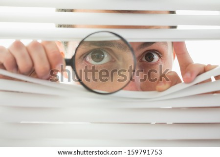 Beautiful brown male eyes spying through roller blind with magnifying glass - stock photo