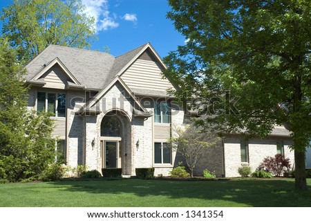 Beautiful brown two story brick home. Typical home in the suburbs of the United States. Just one of many home or house photos in my gallery. - stock photo