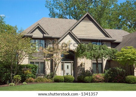 Beautiful brown two story wood and brick home. Typical new home in the suburbs of the United States. Just one of many home or house photos in my gallery. - stock photo