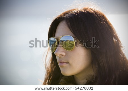 beautiful brunete girl with the sea as the background - stock photo
