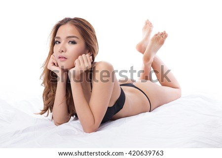 Beautiful brunette asian woman in lingerie and  thong, lying and posing in her bed, isolated on white background - stock photo