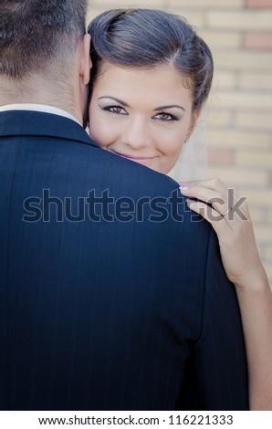 Beautiful brunette bride looking over the grooms shoulder - stock photo