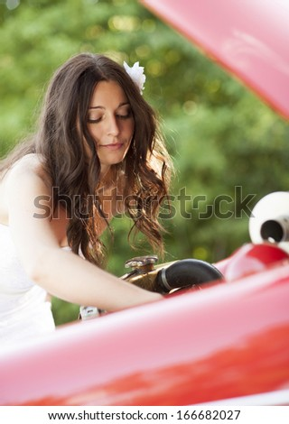 Beautiful brunette bride on a green meadow with retro car - stock photo