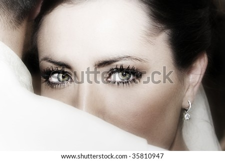 Beautiful brunette bride wearing diamond jewelery looking over the grooms shoulder - stock photo