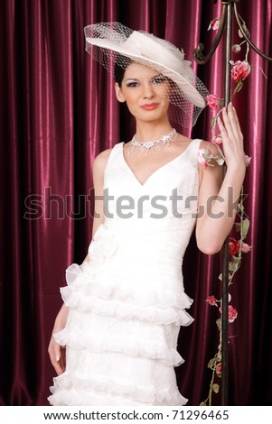 Beautiful brunette bride with hat and veil posing - stock photo