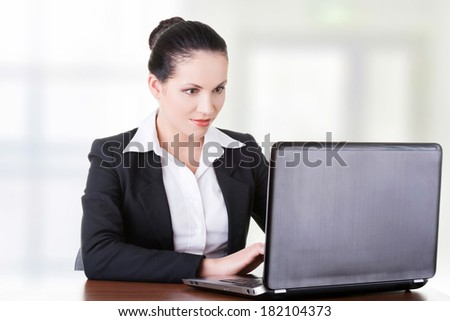 Beautiful brunette businesswoman working on laptop computer - stock photo