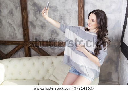Beautiful brunette caucasian fit pregnant woman in casual outfit with curly hairstyle at home making selfie on her phone, smiling. modern interior - stock photo