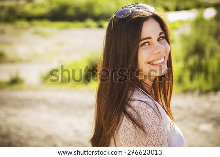 Beautiful brunette caucasian young woman laughing showing perfect teeth on summer sunny day. outdoors. nature. copy space - stock photo