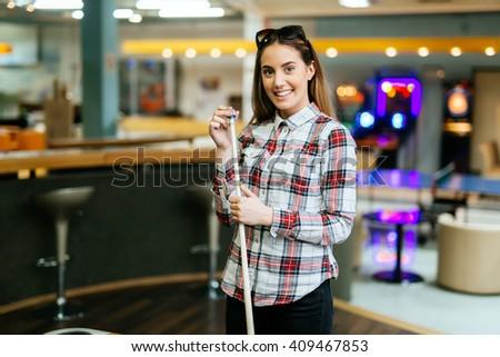 Beautiful brunette chalking billiard cue - stock photo