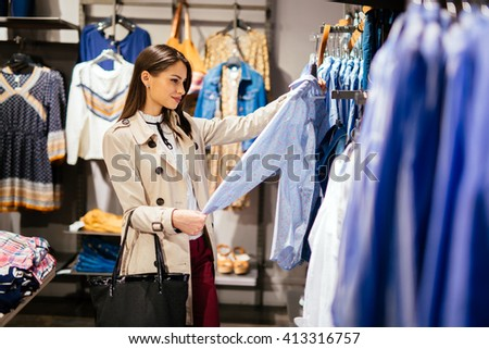 Beautiful brunette choosing and  buying clothes - stock photo