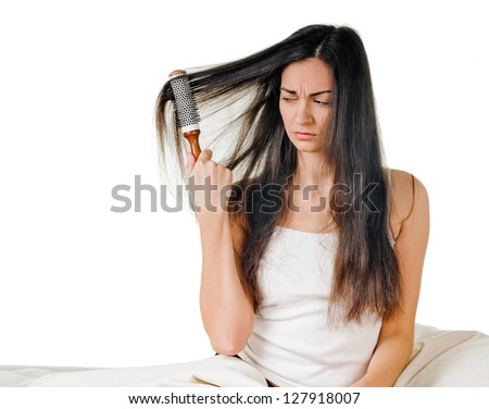 beautiful brunette combing out her long hair - stock photo