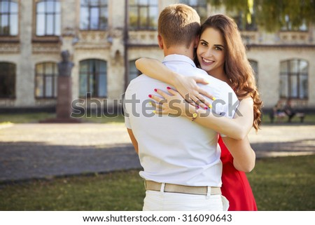 Beautiful brunette couple in love hugging on a date in the park. She in red dress, with curled hairstyle and make up. He in shirt and trousers. Casual style. Outdoors. Warm weather, sunset - stock photo