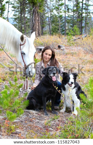 Beautiful brunette cowgirl with her horse and dogs - stock photo