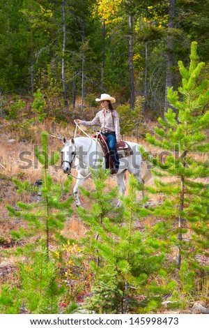 Beautiful brunette cowgirl with her horse on a mountain trail ride  - stock photo