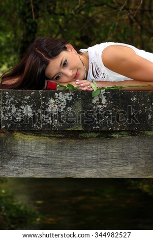 Beautiful brunette daydreaming in the park with red rose beside her. - stock photo
