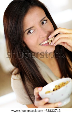 Beautiful brunette eating cereals in the morning - stock photo